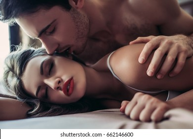 Beautiful passionate couple is having sex on bed.