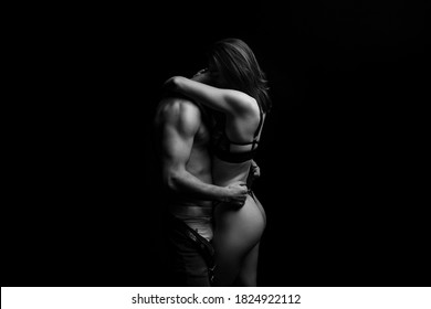 Beautiful passionate couple hugging couple on black background, black and white
