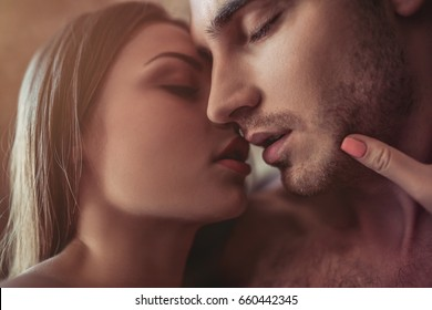 Beautiful passionate couple is kissing on bed. Prelude to sex.