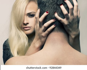 Beautiful passionate girl hugging a man by the neck