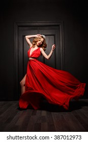 Beautiful and passionate woman in the red evening fluttering dress is capture in motion, the wooden door is on the background
