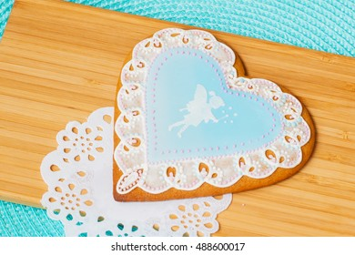 Beautiful pastel blue gingerbread with image of a cute little girl elf and tracery doily, background  wooden planks
