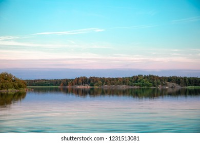 A beautiful pastel blue sunset a few days after midsummer, with a tree-lined horizon and clouds reflected on the water of a cove on the Island of Nicklösa in the Åland Islands, Finland.