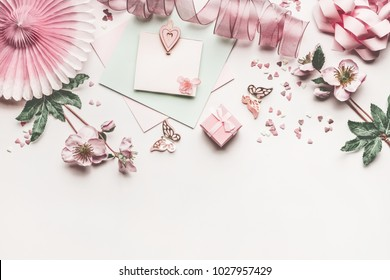 Beautiful pastel pink layout with flowers decoration, ribbon, hearts, bow and card mock up on white desk background, top view, flat lay, border. Wedding invitation or Mother Day greeting concept