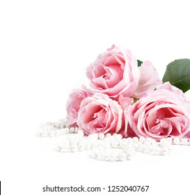 Beautiful pastel pink roses and elegant bridal pearls isolated on white background. Wedding flower bouquet arrangement and classy jewelry. Bright soft clean reception invitation card and banner design