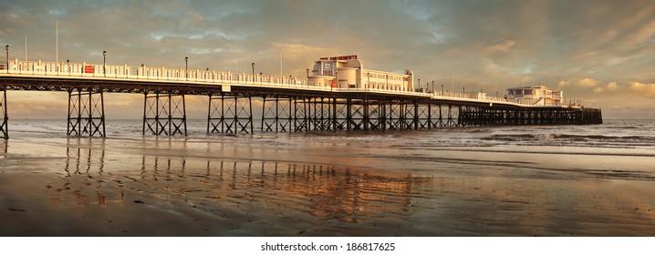 A beautiful pastel sunset illuminates Worthing Pier in Sussex, England