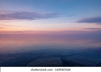 A beautiful pastel sunset over Lake Ontario. The sky reflects purple, blue and orange colors in the water.