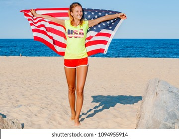Beautiful patriotic happy woman with the American flag held in her outstretched hands on the beach