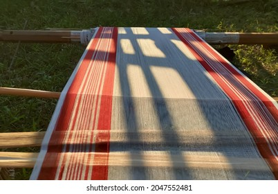 Beautiful pattern and design of red and white threads in traditional handloom from Assam in evening daylight against natural background with partial shadow of nearby objects over it