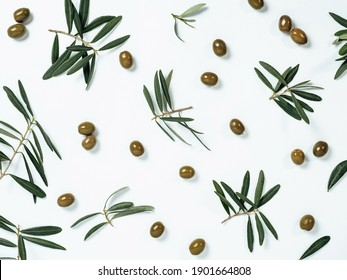 Beautiful pattern with green olives and olives tree leaves and branches on white background. Olive tree fruits and branches as pattern, top view or flat lay.