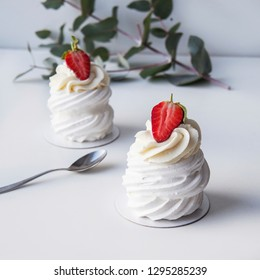 Beautiful pavlova cakes with berrys on a white background with green leaves. Selective focus.  Tasty sweet breackfast. Wedding morning. Meringue with cream and  strawberries.