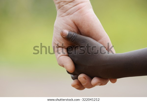 Beautiful Peace Symbol - White Woman Black Child Holding Hands. African Peace Symbol. White woman holds hands with a little native African girl, in Bamako, Mali.