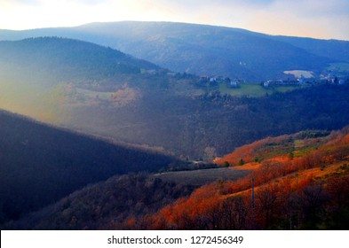 Beautiful peaceful hills with clouds at sunset in Marche region, Italy. Serra San Quirico hills with forest and country in winter. Red forest and blue sky.