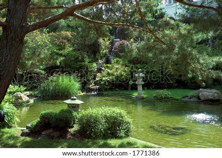 Beautiful And Peaceful Japanese Water Garden. Cascading Waterfall Falling  From The Hill Above And Lined