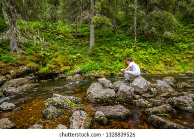 Beautiful and peaceful scene of a young male sitting and contemplating on stone rocks at a forest stream.
