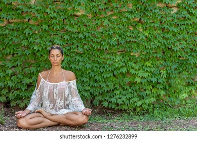 Beautiful, peaceful woman dressed in white romantic blouse practicing yoga in nature. Concept: healthy life, self care, spring resolution, recreation, new beginning, meditation, siddhasana, self love