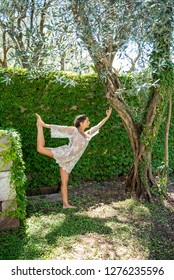 Beautiful, peaceful woman dressed in white romantic blouse practicing yoga in nature. Concept: healthy life, self care, spring resolution, recreation, new beginning, meditation, dancer's pose, love
