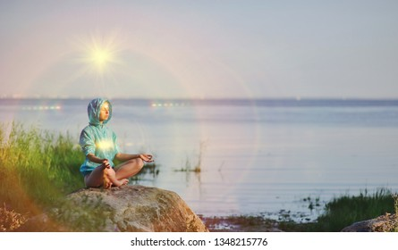 Beautiful peaceful woman sits in a pose of a half lotus practicing yoga meditation, blue summer sky, glowing chakra, eyes closed calm. Kundalini energy exercise. Human spirit, people healing concept