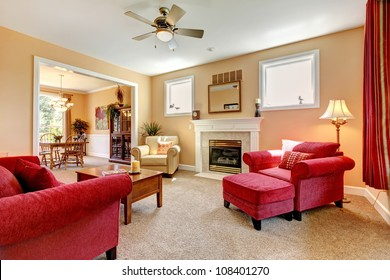 Beautiful peach and red living room interior with fireplace and red furniture.