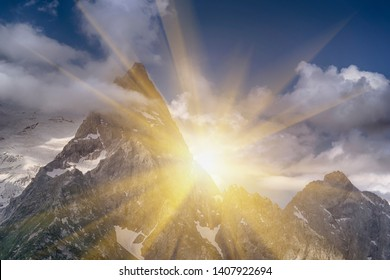 Beautiful peaks of the North Caucasus near the ski resort Dombay, Russia, Karachay-Cherkessia. Bright sun flare in the sky