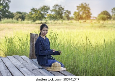 Beautiful peasant girl resting After harvest completed
