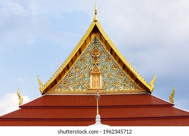 Beautiful pediment of a Buddhist temple decorated with golden images of the Buddha. Thailand, Bangkok