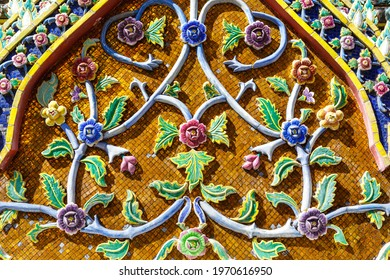 Beautiful pediment of a Buddhist temple decorated with ceramic mosaics depicting flowers. Thailand, Bangkok