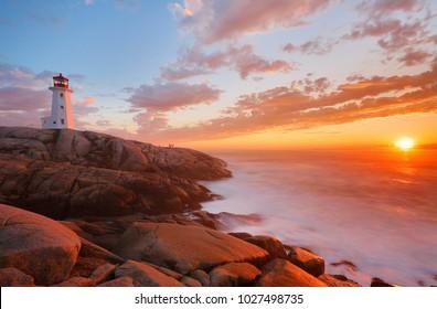 Beautiful Peggy Cove Light House with Sunset, Nova Scotia, Canada. Photo shows tourists watching sunset.