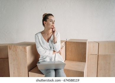 beautiful pensive fashionable businesswoman working with laptop while sitting on wooden cubes