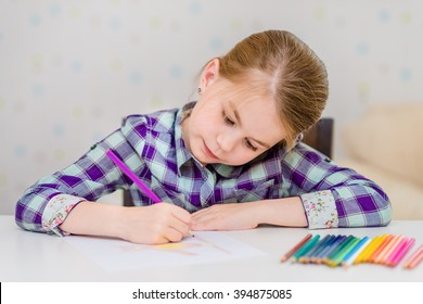 Beautiful pensive little girl with blond hair sitting at white table and drawing with multicolored pencils