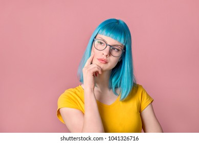 Beautiful pensive young woman with blue color dyed hair with hipster style spectacles thinking in front of pastel studio background.