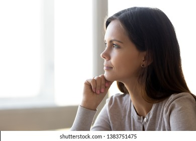 Beautiful pensive young woman look in distance dreaming thinking of future life achievements, thoughtful dreamy girl student lost in thoughts imagining visualizing bright career perspectives