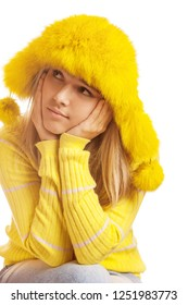 Beautiful pensive young woman in yellow fur hat, isolated on white background.