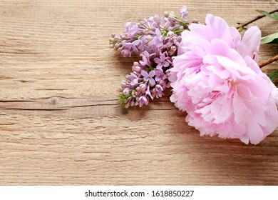 Beautiful peony and lilac on a wooden table, copy space.