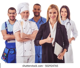 Beautiful people of different professions in uniforms are looking at camera and smiling, isolated on white. Business lady in the foreground
