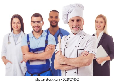 Beautiful people of different professions in uniforms are looking at camera and smiling, isolated on white. Handsome mature cook in the foreground