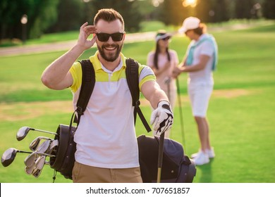 Beautiful people are resting and playing golf, handsome guy in the foreground is looking at camera and smiling