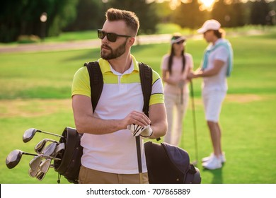 Beautiful people are resting and playing golf, handsome guy in the foreground