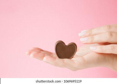 Beautiful, perfect, groomed woman's hand holding chocolate heart. Reaching for candies. Enjoying sweets. Empty place for text or logo on pink pastel background.