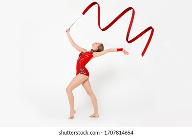 Beautiful performance. Full length portrait of charming gymnast dancing with ribbon on white background