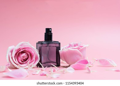 Beautiful perfume bottles on pink background