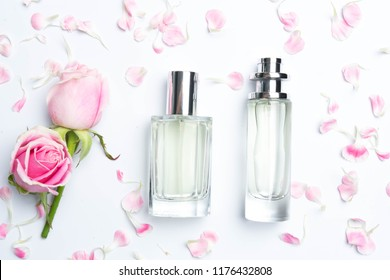 Beautiful perfume bottles  and rose on white background