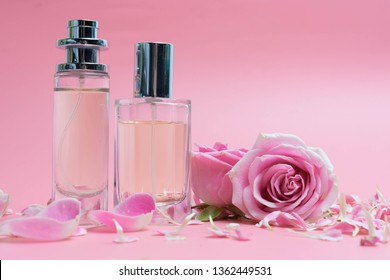 Beautiful perfume bottles  and rose on pink background