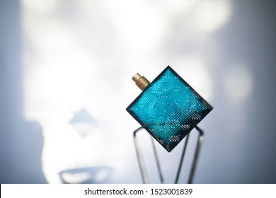 Beautiful perfume for men. In blue bottle placed in front of blue and white background. Banner, copy space, perfume lover.