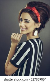 Beautiful persuasive lady tempting with retro sixties fashion style. Enticing smiling young woman in striped attire, red headband and retro updo hairstyle, winking at camera over dark background.