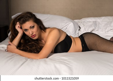 Beautiful petite brunette dressed in black lingerie