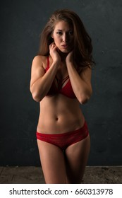 Beautiful petite brunette dressed in red lingerie