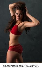 Beautiful petite brunette dressed in red lingerie
