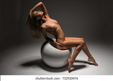 Beautiful petite Czech blonde nude on a white spherical seat