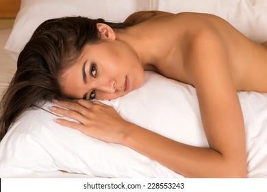 Beautiful petite Eurasian woman nude in bed